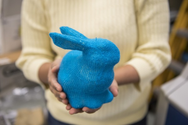 A CMU researcher holds a rabbit knitted by a machine that used patterns generated by a new CMU technology.